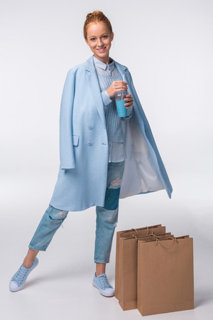 elegant stylish girl in blue autumn outfit holding shopping bags and blue drink, isolated on grey