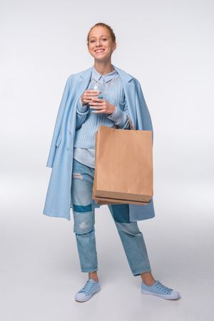 attractive fashionable girl in blue autumn outfit holding shopping bags and blue drink, isolated on grey
