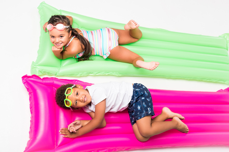 top view of cute multiethnic kids in swimwear lying on swimming mattresses and smiling at camera Stock Photo