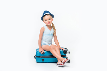 adorable little girl in hat and swimsuit sitting on suitcase and smiling at camera isolated on white