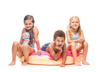 46df92904e8f5 adorable multiethnic kids having fun on swim tube isolated on white