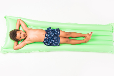 cute little african american boy lying on swimming mattress isolated on white