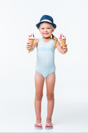 adorable little girl in swimsuit holding ice cream and smiling at camera  Stock Photo