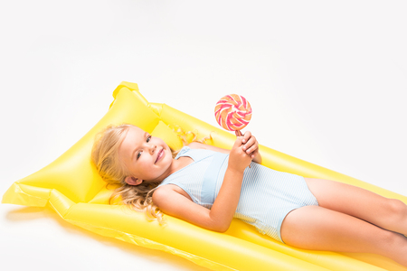 adorable little girl with lollipop lying on swimming mattress and smiling at camera isolated on white