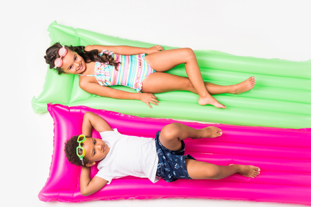 top view of cute multiethnic kids in swimwear lying on swimming mattresses isolated on white