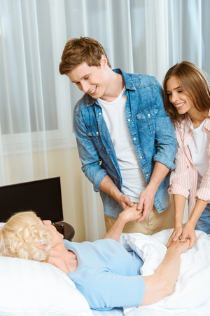 Young smiling couple holding hands of an elderly woman lying in hospital bed Stockfoto