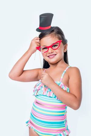 e48e78060b adorable little girl holding false eyeglasses and top hat on party sticks  and looking at camera