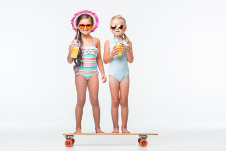 adorable little girls in sunglasses and swimsuits drinking orange juice while standing on skateboard Stockfoto