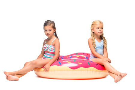 cute little girls in swimsuits sitting on water donut isolated on white