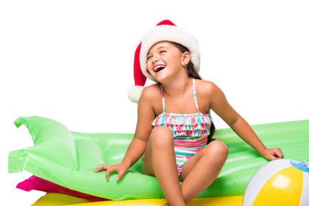 ffb645a4905ce cute smiling little girl in santa hat sitting on swimming mattresses  isolated on white Stock Photo