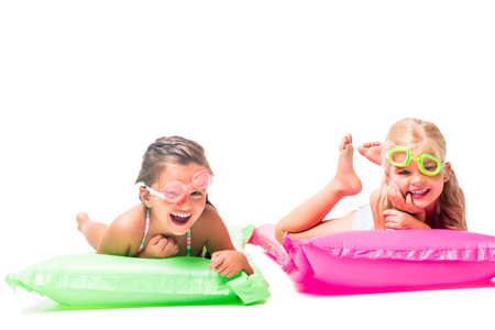 happy little girls lying on swimming mattresses and smiling at camera isolated on white