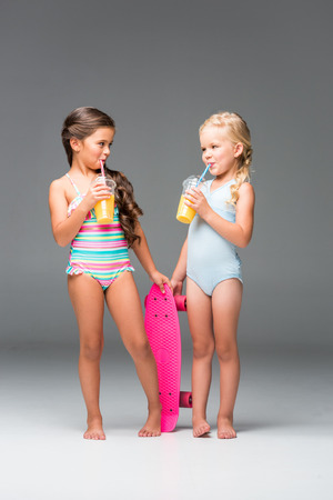 cute little girls in swimsuits drinking orange juice while standing with skateboard isolated on grey Banque d'images