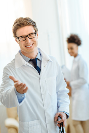 Young doctor in lab coat and glasses smiling cheerfully and holding out his hand Фото со стока