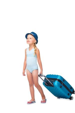 cute little girl in hat and swimsuit holding suitcase and looking away isolated on white Stock Photo