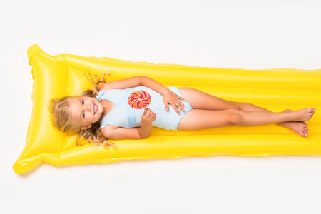 adorable smiling little girl holding lollipop and lying on swimming mattress isolated on white