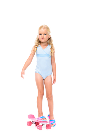 adorable little girl in swimsuit standing on skateboard and looking at camera isolated on white Stockfoto