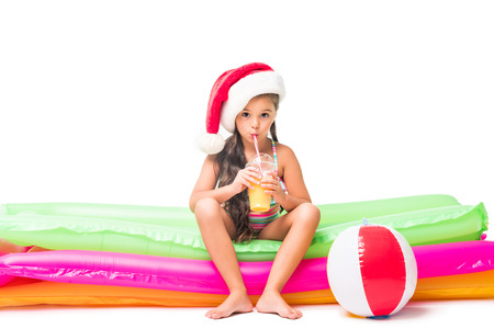 cute little girl in santa hat drinking juice while sitting on swimming mattresses