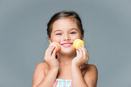 adorable little girl holding macaroons and smiling at camera isolated on grey