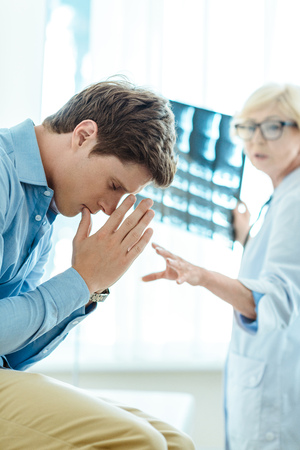 Dissapointed young man praying as the doctor is revealing his diagnosis in background