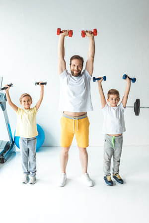 sportive father and sons holding dumbbells in raised hands and smiling at camera Stockfoto