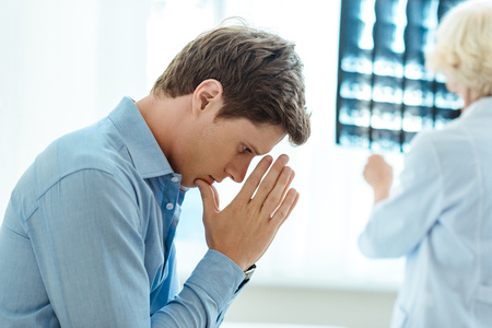 Young man praying while doctor is examining his x-ray photograph in background Stock Photo