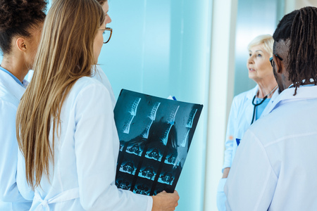A multiracial group of medical interns with x-ray photograph listening to elder doctor