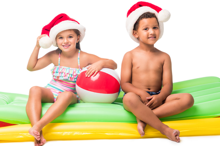 adorable multiethnic kids in santa hats sitting on swimming mattresses isolated on white Stock Photo