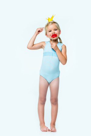 adorable little girl holding false lips and crown on party sticks and looking at camera isolated on white