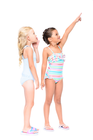 adorable little girls in swimsuits pointing with finger and looking away isolated on white Foto de archivo