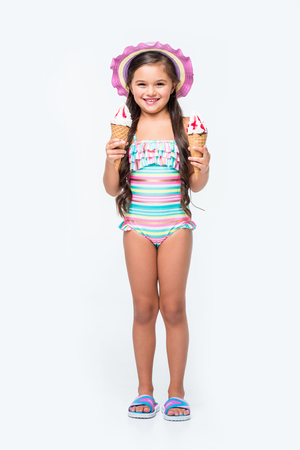 cute little girl in swimsuit holding ice cream and smiling at camera