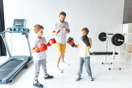 bearded trainer looking at boys in boxing gloves during sparring