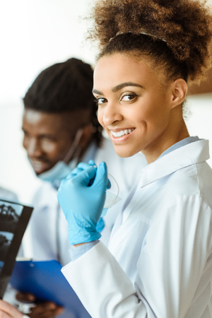 Young african-american doctor in latex gloves and lab coat smiling cheerfully Standard-Bild - 102325217