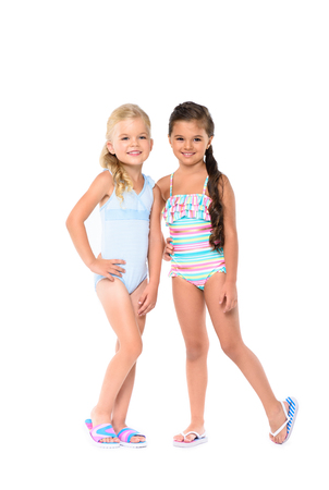 adorable little girls in swimsuits smiling at camera isolated on white