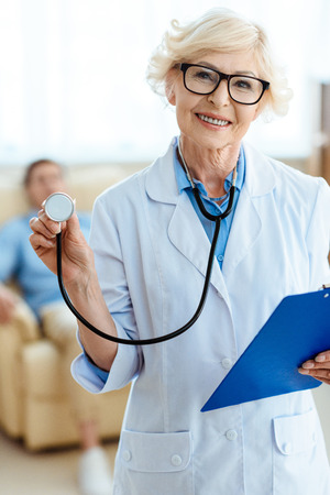 Senior doctor smiling cheerfully and holding stethoscope and clipboard Фото со стока