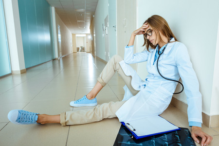 Young doctor in a lab coat sitting on a floor in hospital corridor touching her head