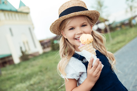 portrait of smiling little girl with ice cream in hand looking at camera Foto de archivo - 102325229
