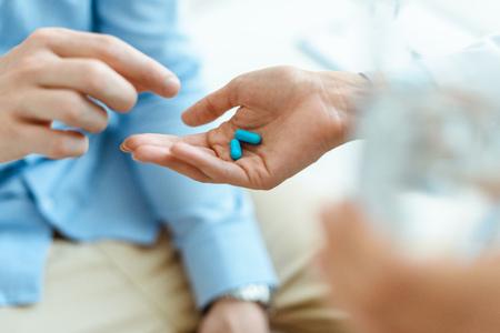 Vista parziale dell'uomo che prende le pillole dalla mano femminile