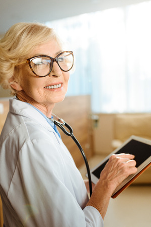 Senior doctor in lab coat and glasses smiling cheerfully and holding a digital tablet Standard-Bild - 102325246