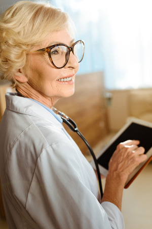 Senior doctor in lab coat and glasses smiling cheerfully and holding a digital tablet Standard-Bild - 102357987