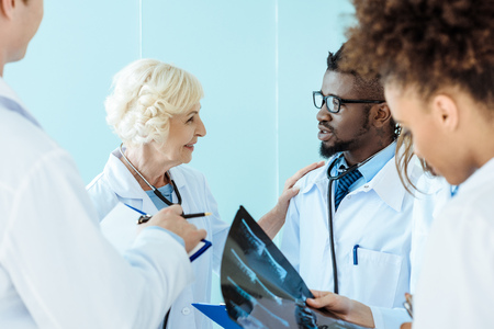 Senior doctor talking to african-american medical intern and touching him on shoulder
