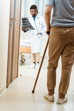 elderly woman with cane walking into a hospital room with young doctor holding x-ray photo Stock Photo