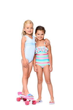adorable little girl in swimsuit standing on skateboard and embracing friend isolated on white