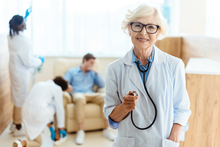 Senior doctor in lab coat and glasses smiling cheerfully and holding stethoscope in hospital enviroment Stock Photo