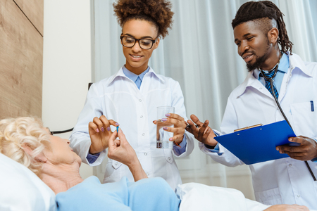 A pair of young doctors handing elderly woman in hospital bed glass of water and a pill Standard-Bild - 102324892