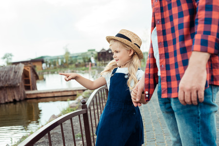 partial view of little girl holding fathers hand and pointing at pond in park