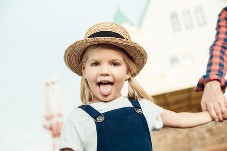 portrait of little girl sticking tongue out and looking at camera