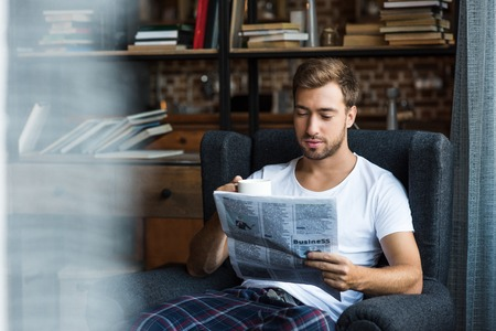 Attractive young man in home clothes sitting in armchair and reading a newspaper Imagens
