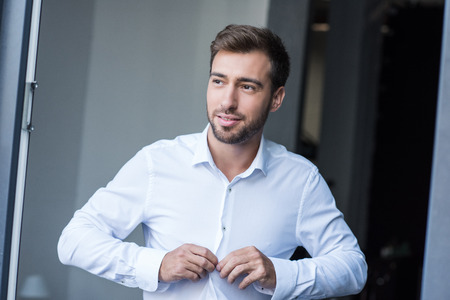 Half-length shot of young smiling man buttoning up a white shirt and looking aside Stock Photo