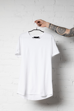 cropped shot of man holding hanger with blank white t-shirt Reklamní fotografie - 102325384
