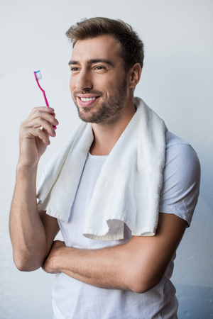 Young smiling man standing with towel on his shoulders and toothbrush in his hand Stock Photo